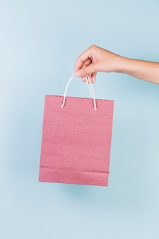 Close-up of a person's hand holding pink paper shopping bag on blue backdrop