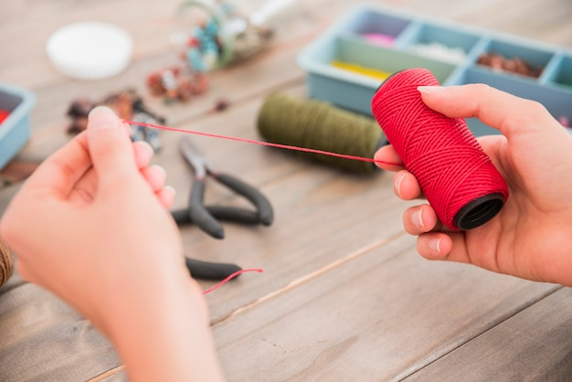 Close-up of a person's hand holding red yarn spool on wooden desk