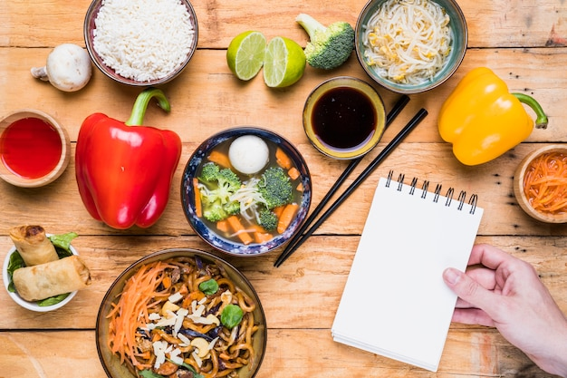 Close-up of a person's hand holding spiral notepad with thai food on table