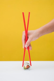 Close-up of a person's hand holding sushi rolls with red chopsticks on table against yellow backdrop
