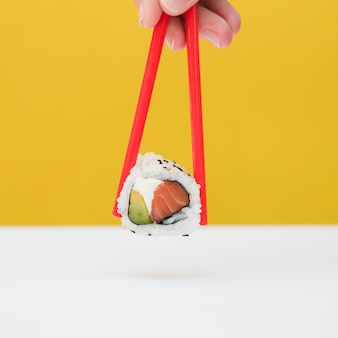 Close-up of a person's hand holding sushi with red chopsticks against yellow backdrop
