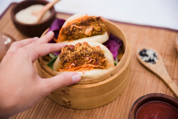 Close-up of a person's hand holding taiwan's traditional food gua bao in steamer