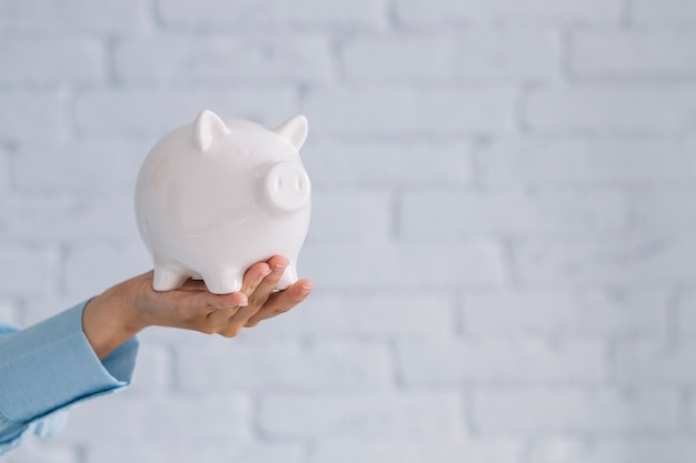 Close-up of a person's hand holding white piggybank