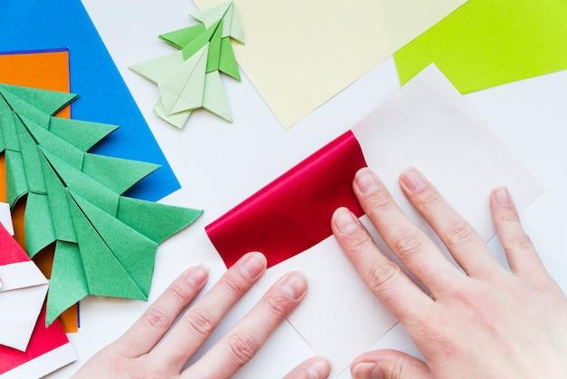 Primo piano della mano di una persona che rende la carta colorata isolato su sfondo bianco