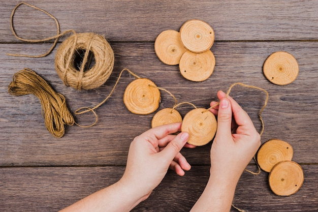 Close-up of a person's hand making garland with wooden ring and thread on wooden table