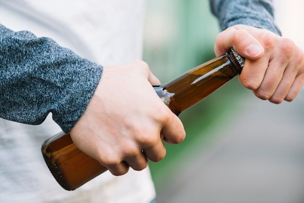 Close-up of a person's hand opening beer bottle