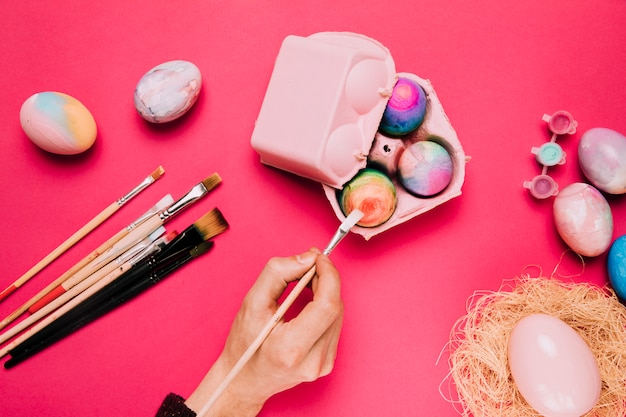 Close-up of a person's hand painting the egg with paint brush in the carton on pink backdrop