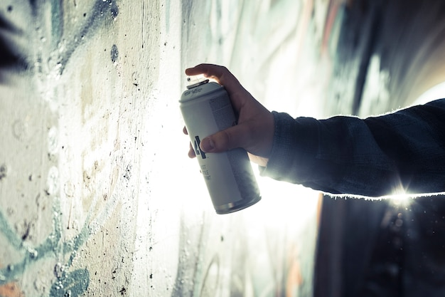 Close-up of a person's hand painting graffiti with spray can on wall