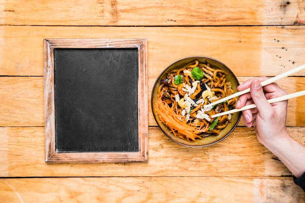 Close-up of a person's hand picking the noodles with chopsticks near the blank slate on table