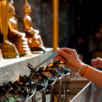 Close-up of a person's hand pouring oil into an oil lamp at wat phrathat doi suthep, chiang mai, thailand