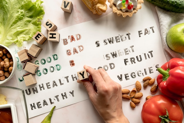 Close-up of a person's hand printing unhealthy text on paper with food and blocks