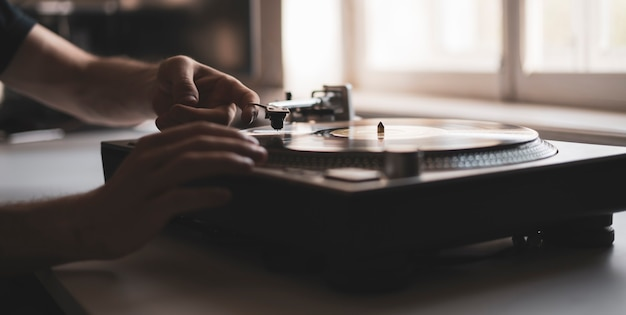 A close up person's hand put the needle on a record, playing vinyl disc at the party