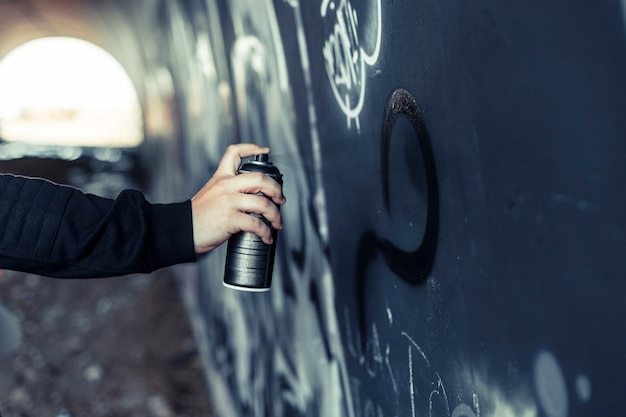 Close-up of a person's hand spraying paint with aerosol can on graffiti wall