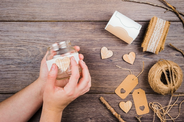 Close-up of a person's hand sticking the wooden heart on transparent bottle over the wooden desk