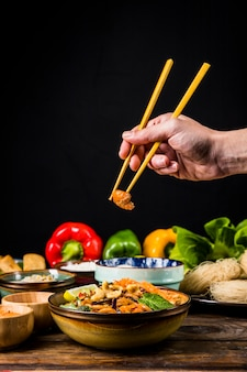Close-up of person's hand taking shrimp from prepared noodles in the bowl on wooden desk against black backdrop