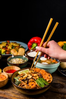 Close-up of a person's hand taking thai food with chopsticks against black background