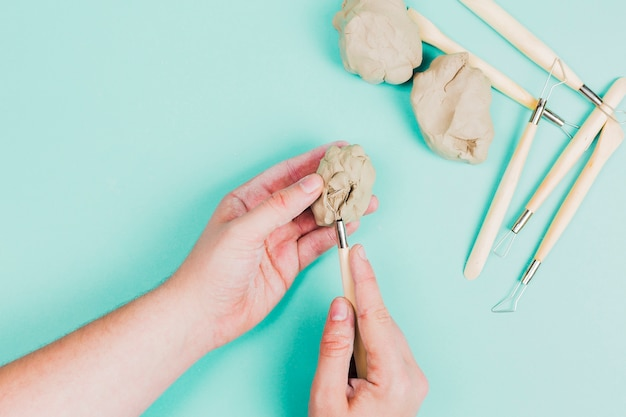 Close-up of a person's hand using sculpting tools on mint green background