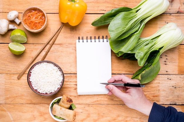 Close-up of a person's hand writing on blank white spiral notepad with thai food on wooden table