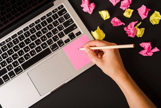 Primo piano della mano di una persona che scrive sulla nota adesiva rosa sul portatile su sfondo nero