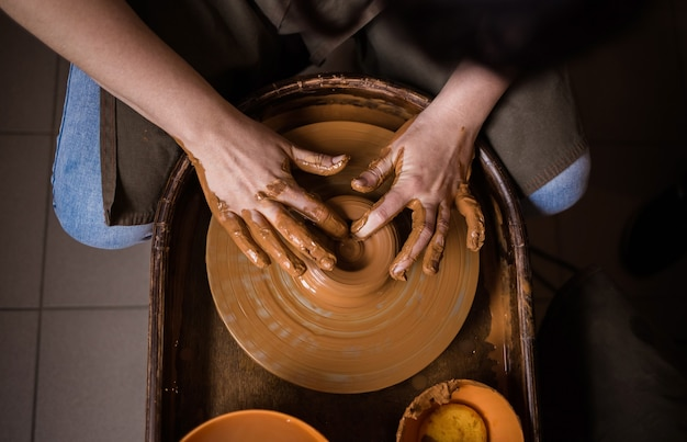 Close-up of a person's hands making a bowl out of clay on a loom in a room