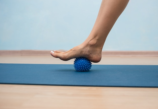 Close-up of a person's leg doing exercises with a massage ball with needles