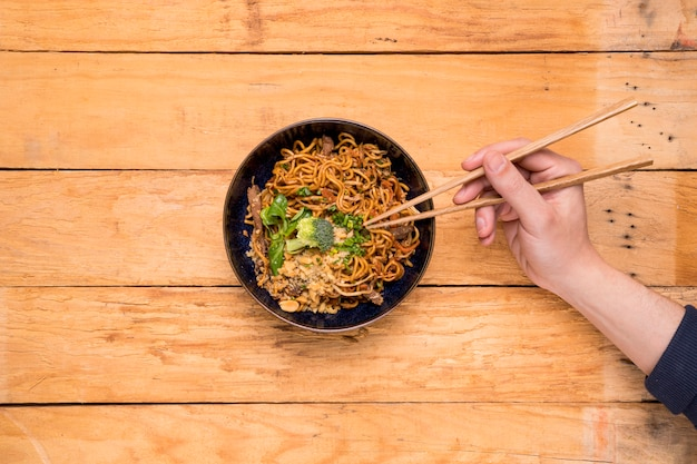 Close-up of a person's picking the noodles with chopsticks on wooden plank