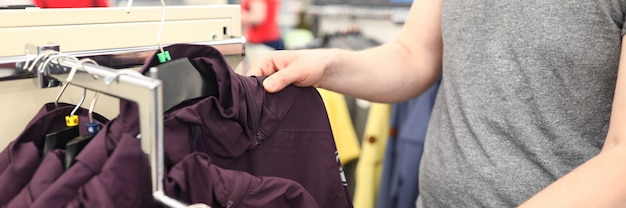 Close-up of person in shopping centre. man choosing outerwear in store. stylish and comfy jackets on stamps. adult spending money on clothes. wardrobe change concept