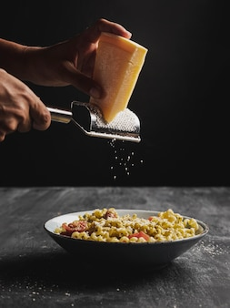 Close-up person shredding cheese on pasta