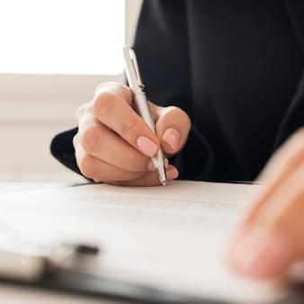 Persona del primo piano che firma un certificato