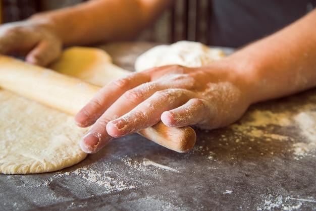 Close up person spreading dough