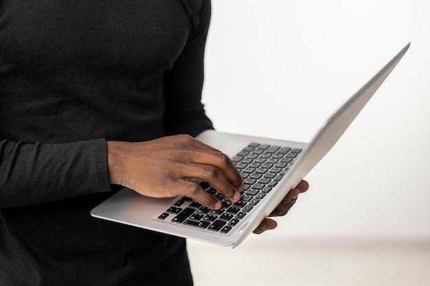 Persona del primo piano in piedi e utilizzando un computer portatile