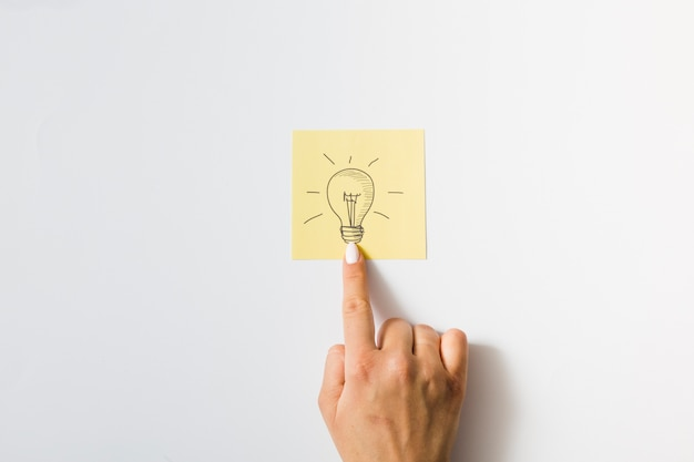 Close-up of a person touching finger on drawn light bulb over the sticky note