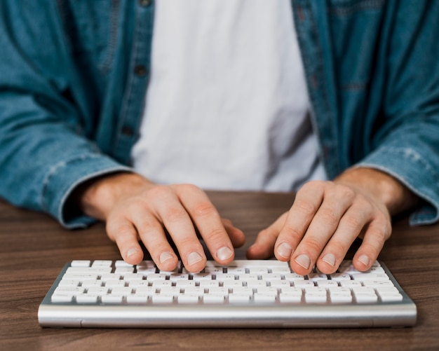 Крупным планом человек с помощью беспроводной клавиатуры mac