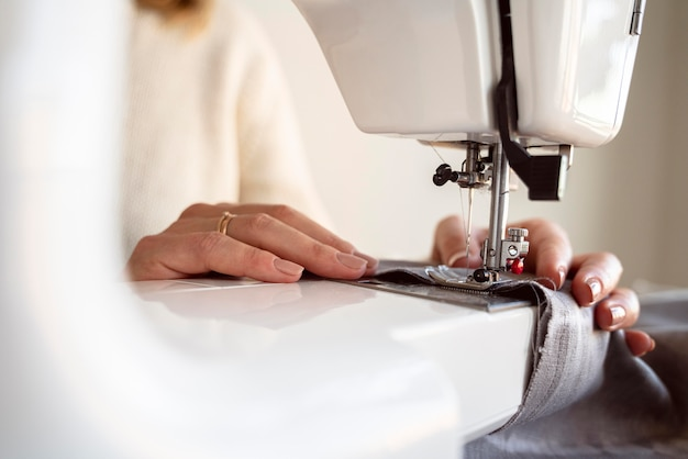 Close-up person using sewing machine