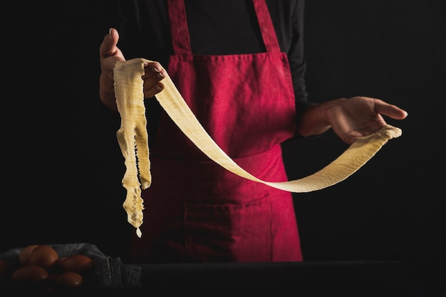 Close-up person with apron holding dough