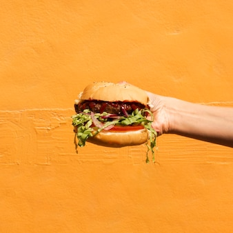 Close-up person with burger and orange background