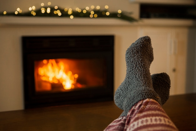 Close-up person with cozy clothes near the fireplace