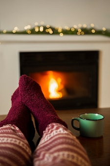 Close-up person with cozy socks near the fireplace