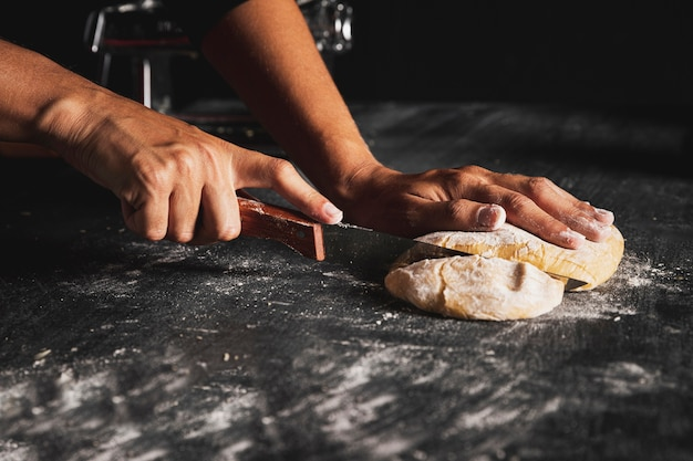 Close-up person with knife cutting dough