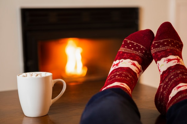 Close-up person with marshmallow drink and cozy socks