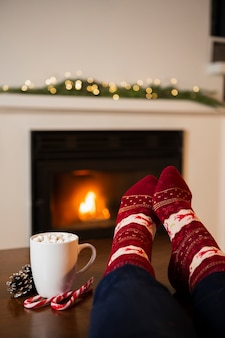 Close-up person with marshmallow drink near the fireplace