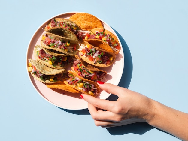 Close-up person with plate full of tacos