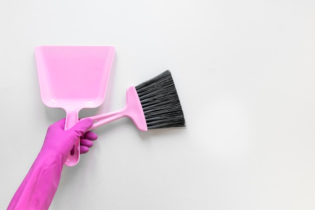 Close-up person with purple gloves holding small broom