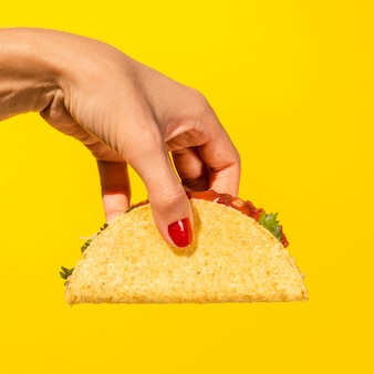 Close-up person with taco and yellow background