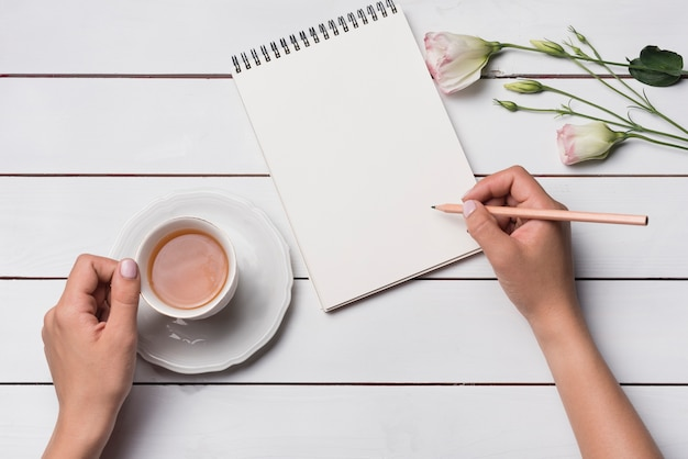 Close-up of a person writing on notepad with cup of teat over wooden desk
