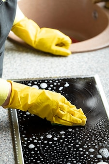 Close up person in yellow rubber gloves cleaning house wipes kitchen worktop using degreaser spray detergent stove cleaner, washes induction stove with sponge