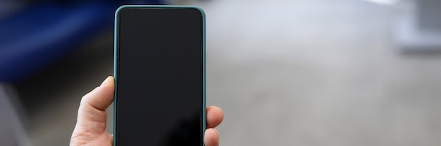 Close-up of persons hand holding modern smartphone with black screen. mockup style. copy space in right side. device for fun or work. technology and entertainment concept