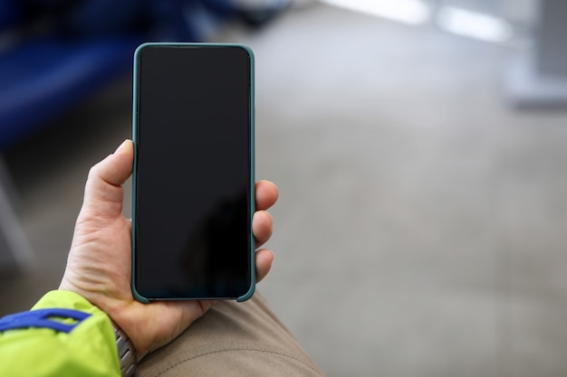 Close-up of persons hand holding modern smartphone with black screen.