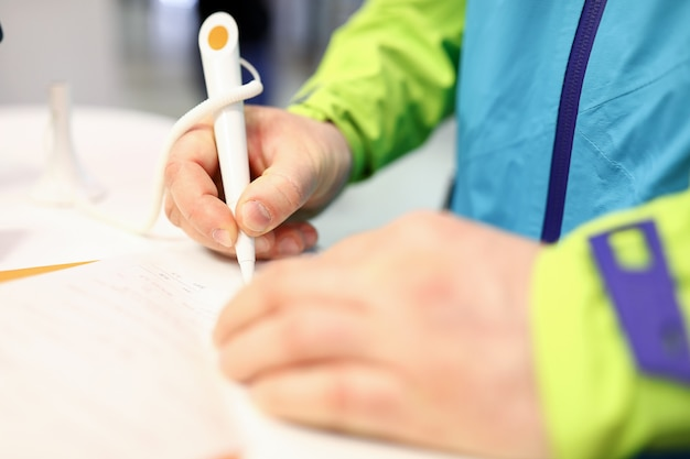 Close-up of persons hand signing check or receipt with white pen. man in bright jacket. male in bank filling important form on paper. money and accountability concept