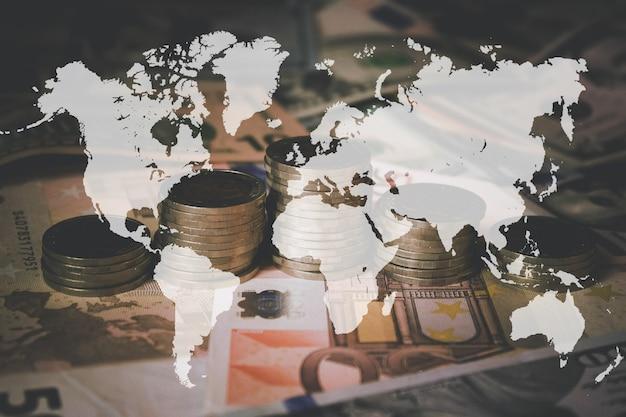 배경으로 지폐의 투시도를 닫습니다. 동전 스택, 어두운 배경에 가상 홀로그램 세계 지도. 돈 절약, 금융의 개념입니다. 투자 아이디어. 성공.